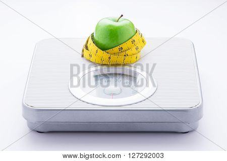 concept of eating healthy and maintaining good body. Apple and tape measure on bathroom scale isolated on white background