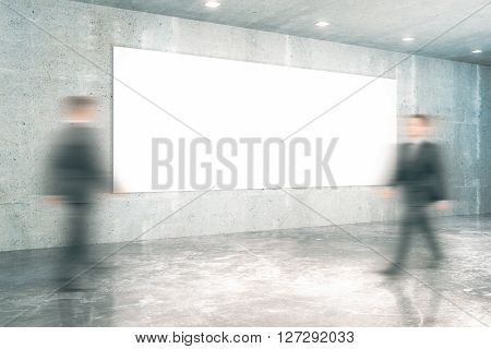 Blank board and two businessmen walking past it in concrete interior. Mock up 3D Rendering
