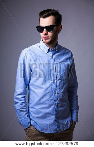 Portrait Of Young Handsome Man In Sunglasses Posing Over Gray