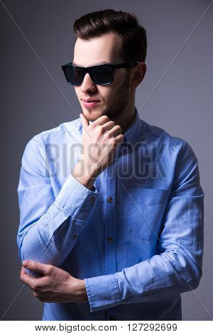 Young Handsome Man In Sunglasses Thinking About Something Over Gray