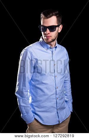 Young Handsome Man In Sunglasses Posing Isolated On Black