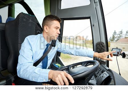 transport, transportation, navigation and people concept - bus driver entering address to gps navigator