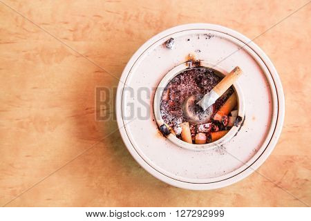 Overhead View Of Cigarette Butts In Ashtray Placed On Table