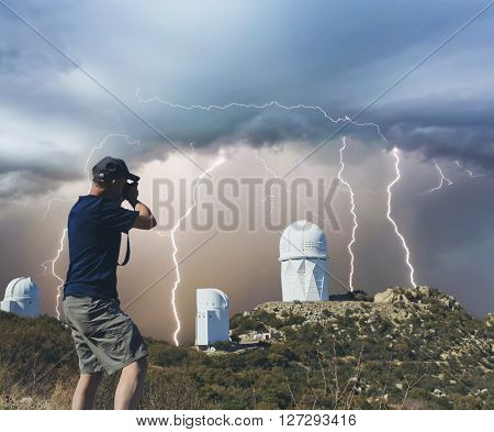 A Man Photographs Mountaintop Observatory Telescopes During a Monsoon Thunderstorm