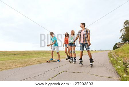 summer holidays, leisure, sport, love and people concept - group of happy teenage friends with rollerskates and longboards