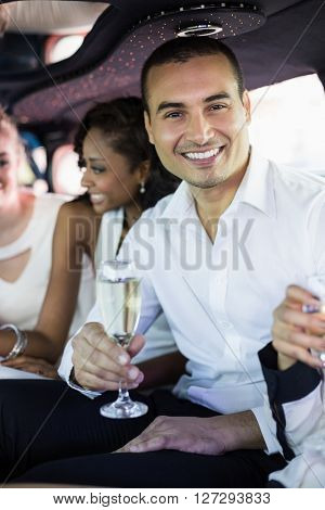 Well dressed man drinking champagne in a limousine