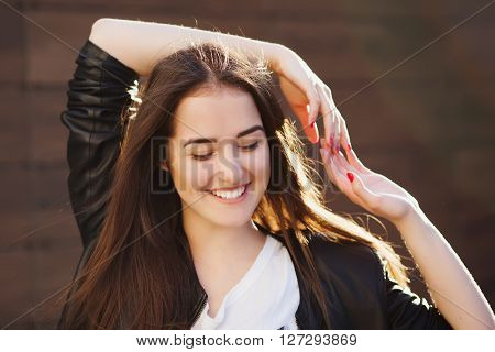 Lovely portrait of pretty smiling woman. Girl's hair backlit by the yellow hot sunlight. She closed her eyes and smiling.
