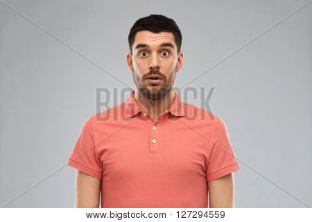 emotion, advertisement and people concept - surprised man in polo t-shirt over gray background
