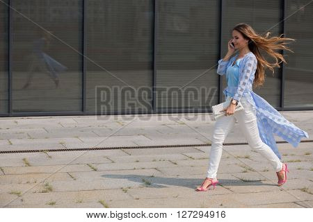 Businesswoman with long brown hair speaking over smart phone and hurrying up. Lady with blue coat on walking along the office building.