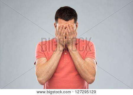people, crisis, emotions and stress concept - man in t-shirt covering his face with hands over gray background