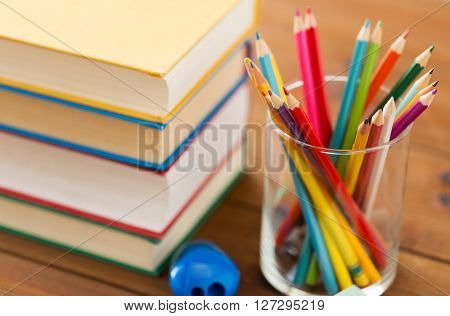 education, school, drawing, creativity and object concept - close up of crayons or color pencils with books and sharpener on wooden table