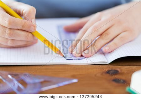 school, education, people and learning concept - close up of student hands with ruler and pencil drawing line in notebook