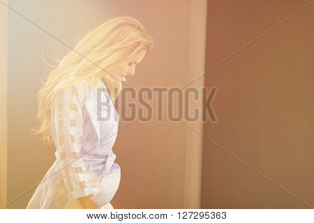 Picture of beautiful lady with long brown hair stooping her head among huge columns of building. Fashionable girl waiting for her husband.