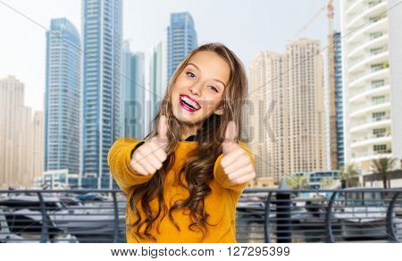 people, gesture, style and fashion concept - happy young woman or teen girl in casual clothes showing thumbs up over dubai city street background