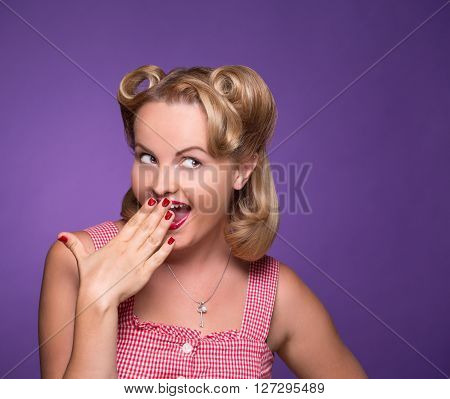 Suspicious pin-up girl smiling and closing her mouth isolated on violet. Sexy blond model looking away and thinking about secrets.