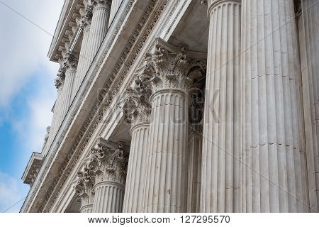 St Paul's Cathedral in London against a cloudy blue sky. Detail of ornate pillars in close-up