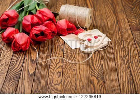 Tulips bouquet and decor with coarse thread on the wooden background.