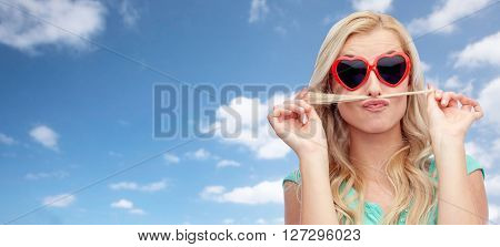 emotions, expressions, hairstyle and people concept - smiling young woman or teenage girl making mustache with strand of hair over blue sky and clouds background