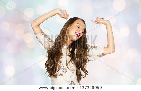 people, style, holidays and fashion concept - happy young woman or teen girl in fancy dress with sequins and long wavy hair dancing at party over holidays lights background