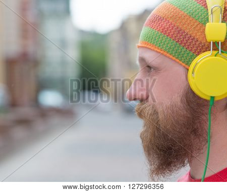 Close-up portrait of freelancer man's left cheek. Man in multi-coloured hat using earphones for listening to the music.