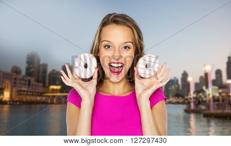 people, travel, tourism, junk food and fast food concept - happy young woman or teen girl in pink dress with donuts over evening city waterfront background