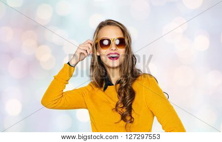 people, style and fashion concept - happy young woman or teen girl in casual clothes and sunglasses over holidays lights background