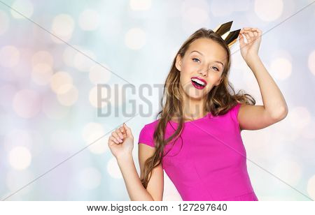 people, holidays and fashion concept - happy young woman or teen girl in pink dress and princess crown over holidays lights background