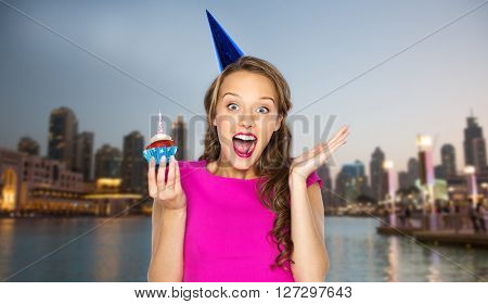 people, holidays, emotion, expression and celebration concept - happy young woman or teen girl in pink dress and party cap with birthday cupcake over evening city waterfront background