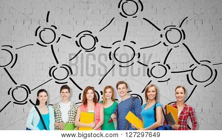 education, school and people concept - group of smiling teenage students with folders and school bags over gray brick wall background with network drawing