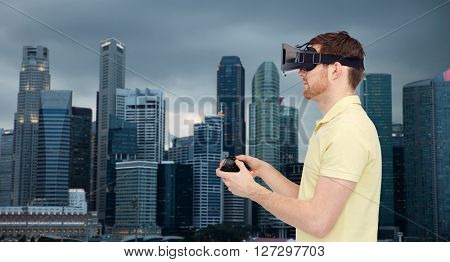 3d technology, virtual reality, travel, entertainment and people concept - happy young man with virtual reality headset playing with game controller gamepad over singapore city background