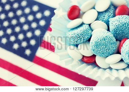 american independence day, celebration, patriotism and holidays concept - close up of glazed sweet candies with flag and paper stars decoration at 4th july theme party
