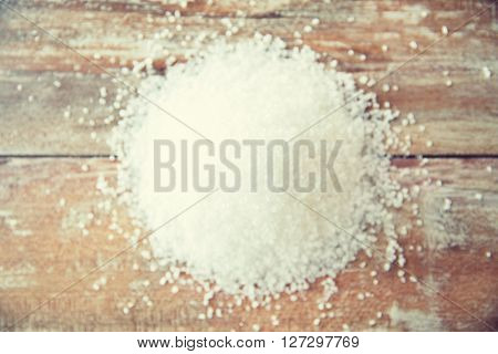 food, junk-food, cooking and unhealthy eating concept - close up of white sea salt heap on wooden table