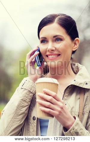 drinks, leisure, technology and people concept - smiling woman with coffee calling and talking on smartphone in park