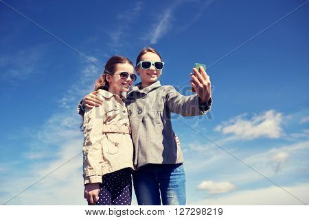 people, children, technology, friends and friendship concept - happy girls with smartphone taking selfie outdoors