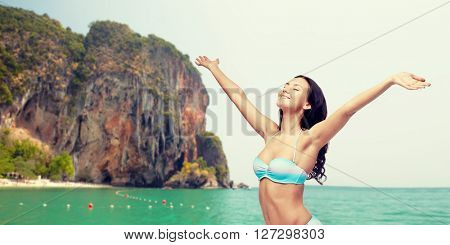 people, summer and beach concept - happy young woman in bikini swimsuit with raised hands looking up over sea and rock background