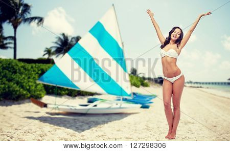 people, summer vacation, tourism and travel concept - happy young woman in white bikini swimsuit posing or dancing with raised hands over sailing boats on tropical beach background