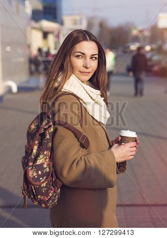Portrait of a beautiful young brunette woman looking into the distance, in a coat and a scarf, standing in the street in spring or autumn. In his hand a cup of hot tea or coffee, fashion shoulder bag.