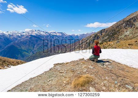 Hiker Kneeling And Resting On The Scenic Mountain Summit
