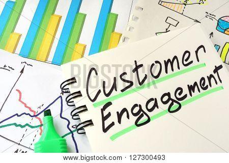 Customer Engagement written on a notepad sheet.