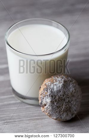 Photo of glass of milk and cookie on wooden table