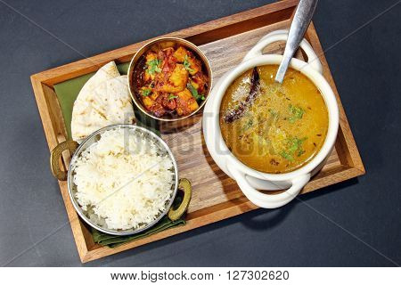 Overhead view of an Indian vegetarian meal comprising of yellow lentil daal or soup with Karahi paneer rice and chapati on a tray.