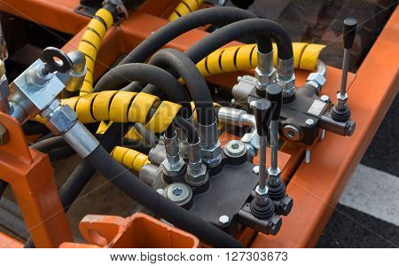 Hydraulic tubes fittings and levers on control panel of lifting mechanism