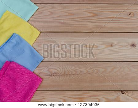 Multicoloured rags for cleaning a top view on wooden table