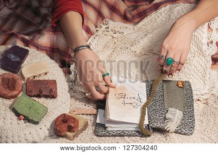 Woman hands in boho rings laying on the lace and open the soap receipt book. Multicolour home made soap laying near.