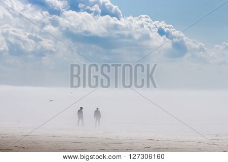 Russia Siberia Novosibirsk region Ob river - April 24 2016: two men walk in the fog along the river Bank