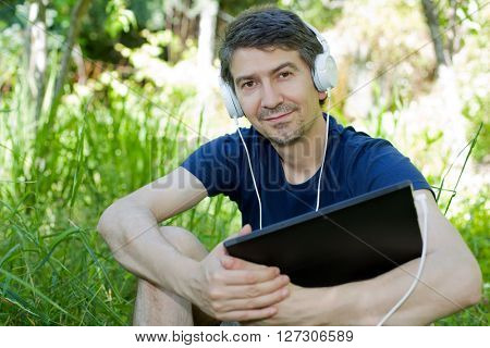 young man relaxing with a tablet pc and phone on a the park, outdoor