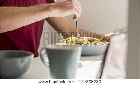Closeup of a man swirling spaghetti with pesto sauce with a fork sitting at white desk with coffee mug in front of the pasta plate.