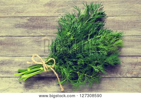 Sprigs of fresh dill with water drops on wooden background. Selective focus.