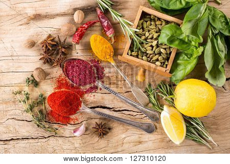 various spices and herbs on wood background