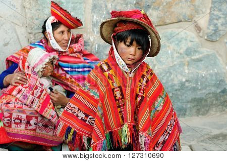 CUSCO PERU - APRIL 04 2012: Sad and poor Peruvian children in traditional garments in the Sacred Valley in South America in April 04 2012